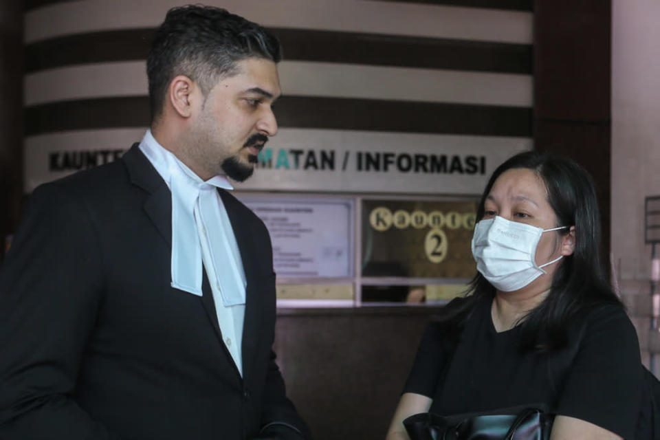 Lawyer V. Vemal Arasan speaks to Simon Momoh's wife, Low Kar Hui at the Shah Alam High Court April 23, 2021. — Picture by Yusof Mat Isa