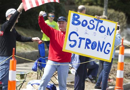 Apr 21, 2014; Boston, MA, USA; A man holds up a Boston Strong poster along the race course during the 2014 Boston Marathon. David Butler II-USA TODAY Sports