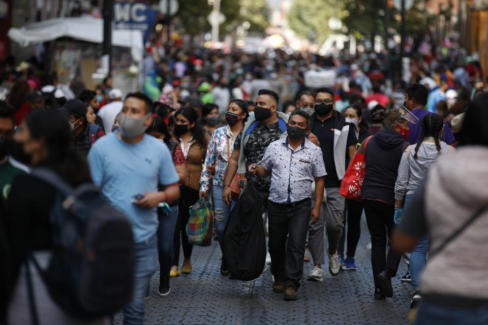Shoppers, the vast majority wearing protective face masks, crowd a street in a commercial district of central Mexico City, Saturday, Dec. 5, 2020. With hospitals once again filling up with COVID-19 patients, Mexico City's mayor on Friday urged people to stay at home as much as possible and authorized checkpoints to limit the number of people entering the capital's colonial-era downtown at one time.(AP Photo/Rebecca Blackwell)