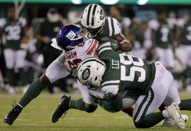 New York Jets linebacker Avery Williamson, top, and linebacker Darron Lee (58) tackle New York Giants tight end Evan Engram (88) who fumbled the ball on the play during the second quarter of an NFL football game, Friday, Aug. 24, 2018, in East Rutherford, N.J. (AP Photo/Julio Cortez)
