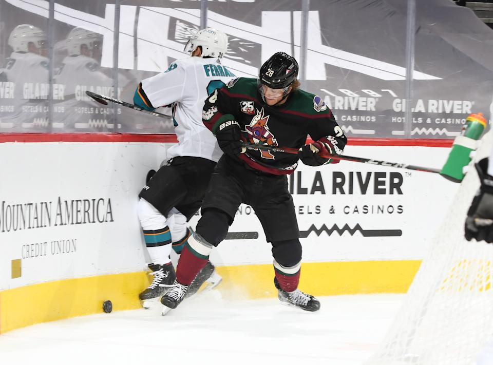 GLENDALE, ARIZONA - MARCH 26: Dryden Hunt #28 of the Arizona Coyotes checks Mario Ferraro #38 of the San Jose Sharks into the boards while battling for a loose puck at Gila River Arena on March 26, 2021 in Glendale, Arizona. (Photo by Norm Hall/NHLI via Getty Images)