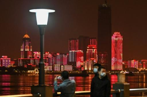People wearing facemasks walk near the Yangtze River in Wuhan, epicentre of the coronavirus, which reported no new deaths from the disease for the first time since January