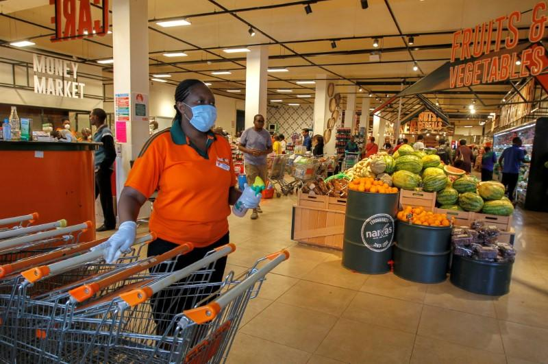 FILE PHOTO: Worker disinfects shopping trolleys as customers shop in the Naivas Supermarket in Nairobi