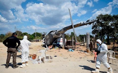 Technicians work at the site of the accident where a military helicopter fell on a van - Credit: ALFREDO ESTRELLA/AFP/Getty Images