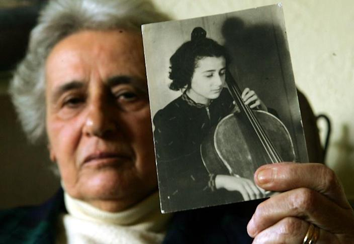 Holocaust survivor Anita Lasker-Wallfisch, pictured here in 2005, holds up a portrait of herself playing the cello in Berlin before World War II (AFP Photo/JIM WATSON)