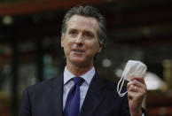 FILE - In this June 26, 2020, file photo, California Gov. Gavin Newsom displays a face mask as he urges people to wear them to fight the spread of the coronavirus during a news conference in Rancho Cordova, Calif. Gov. Newsom announced a new, color-coded process Friday, Aug. 28, 2020, for reopening California businesses amid the coronavirus pandemic that is more gradual than the state's current rules to guard against loosening restrictions too soon. Counties will move through the new, four-tier system based on their number of cases and percentage of positive tests. It will rely on those two metrics to determine a tier: case rates and the percentage of positive tests. (AP Photo/Rich Pedroncelli, Pool, File)
