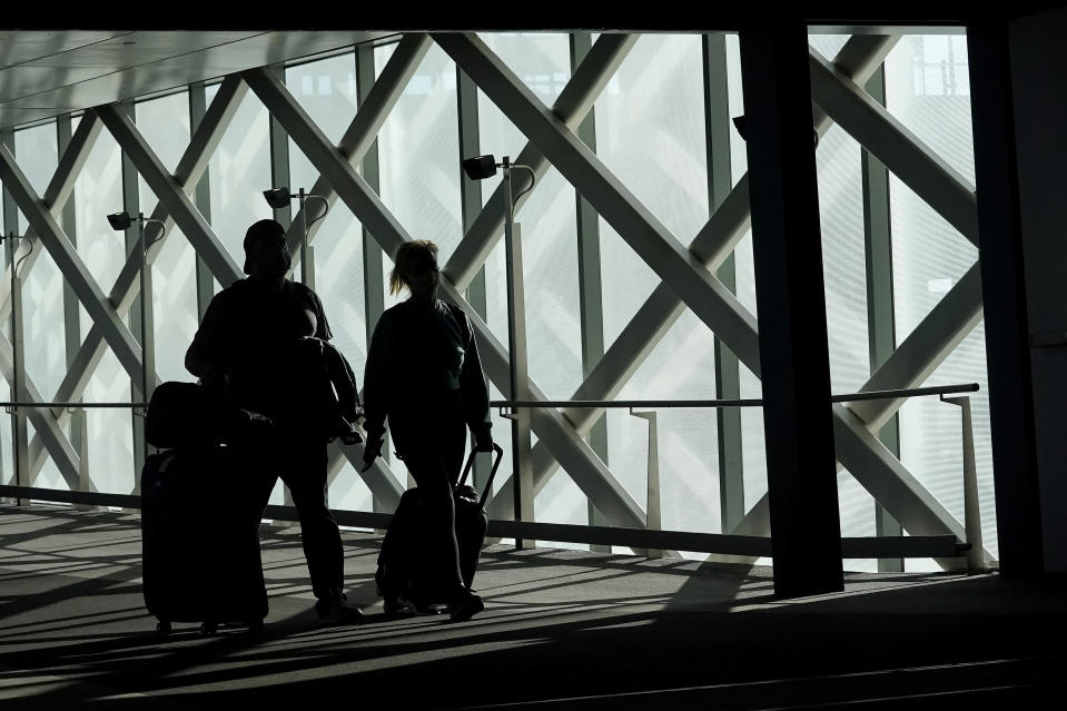 Travelers walk toward terminals at San Francisco International Airport during the coronavirus outbreak in San Francisco, Tuesday, Nov. 24, 2020. (AP Photo/Jeff Chiu)