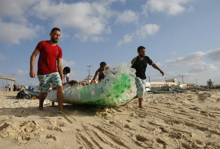 Palestinian fisherman Mouad Abu Zeid (R) and his friends carry his boat, made of 700 plastic bottles, into the sea off Rafah in the southern Gaza Strip on August 14, 2018