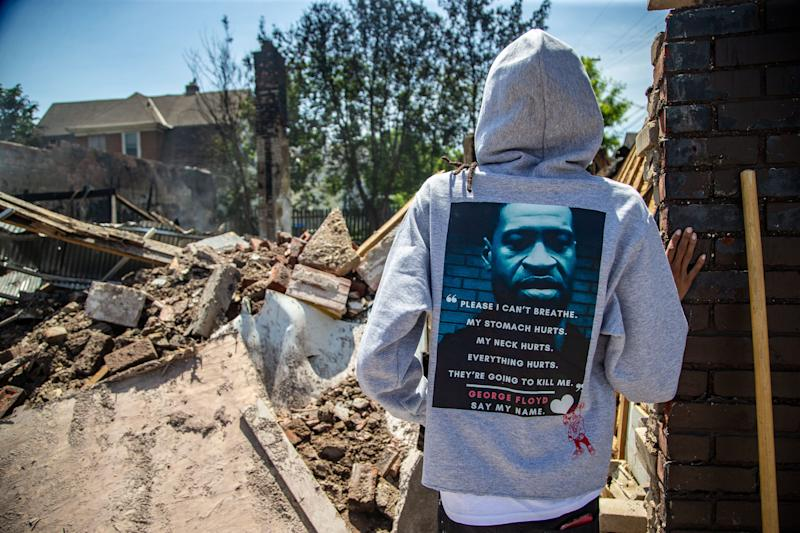 Brandy Moore wares a George Floyd hoodie as she stands over the rubble of her clothing store Levels Sunday, May 31, 2020. Her Minneapolis business was looted and burned during protests over the death of George Floyd.