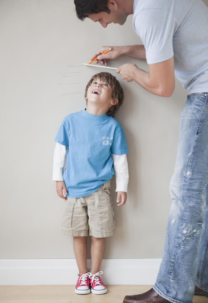 Father measuring son's height against wall