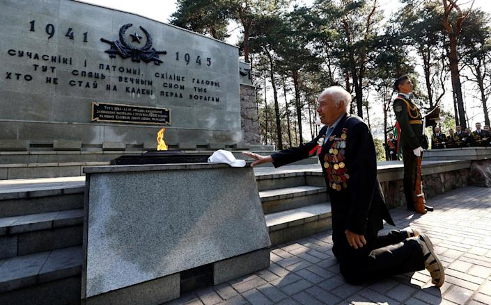 <p>Stanislav Shantor, 90, World War II veteran, knees at the memorial during the reburial of the remains of 147 Soviet prisoners of war, before the celebration of Independence Day, which is marked on Sunday, in Minsk, Belarus, July 1, 2016. (Photo: Vasily Fedosenko/REUTERS) </p>