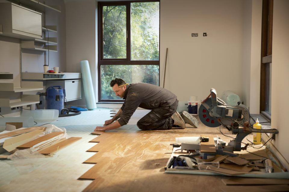 Construction worker laying hardwood flooring in house