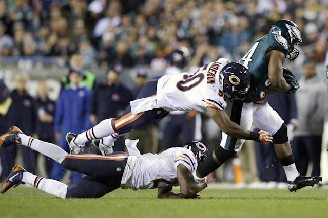 Philadelphia Eagles' Bryce Brown, right, breaks free of Chicago Bears' James Anderson, top left, and Roc Carmichael during the second half of an NFL football game, Sunday, Dec. 22, 2013, in Philadelphia. (AP Photo/Michael Perez)