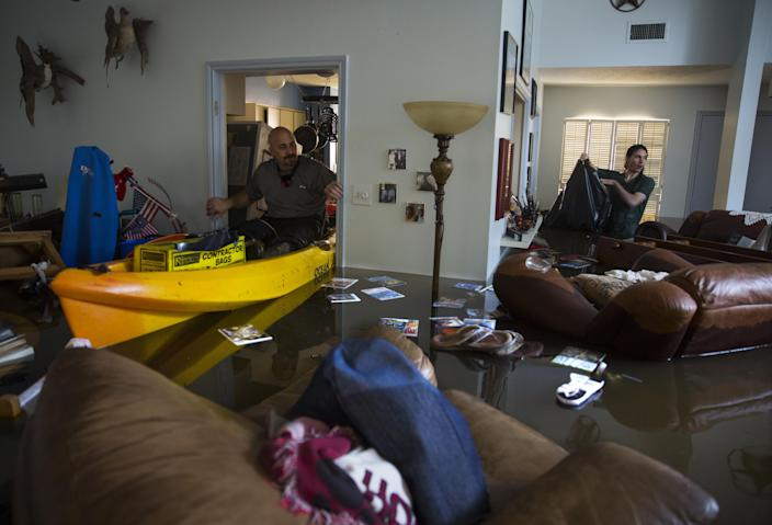 The Kosers' son Larry Jr. and their grandson Matthew look for important papers and heirlooms in the flooded house. (Photo: Erich Schlegel/Getty Images)