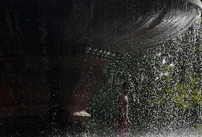 An Indian youth stands under a fountain near India Gate amid soaring temperatures in New Delhi, on May 27, 2015 (AFP Photo/Sajjad Hussain)