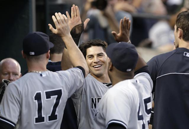 New York Yankees' Jacoby Ellsbury, center, celebrates after scoring on a Derek Jeter double against the Detroit Tigers in the third inning of a baseball game in Detroit Wednesday, Aug. 27, 2014. (AP Photo/Paul Sancya)