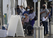 Orange County residents wait in line outside tents for a COVID-19 vaccine at the Toy Story parking lot at the Disneyland Resort Wednesday, Jan. 13, 2021, in Anaheim, Calif. The parking lot is located off Katella Avenue and sits southeast of Disneyland. California is immediately allowing residents 65 and older to get scarce coronavirus vaccines, Gov. Gavin Newsom announced Wednesday. (AP Photo/Damian Dovarganes)