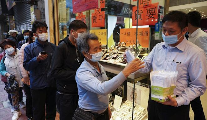 Masks are handed out from a shop in Percival Street as several companies assume the responsibility of supplying residents with health products. Photo: Robert Ng