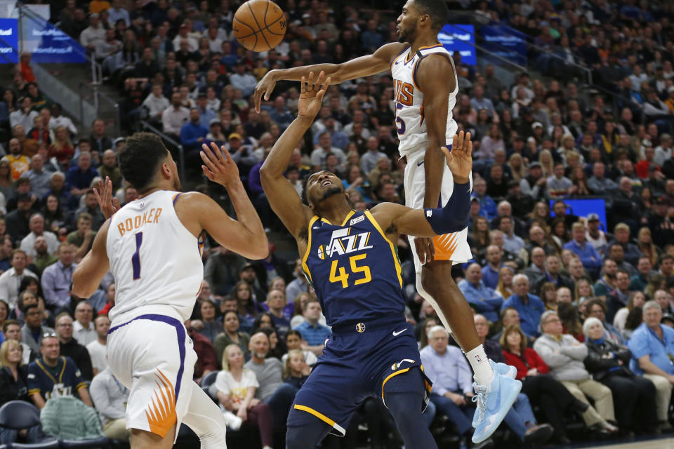 Utah Jazz guard Donovan Mitchell (45) loses the ball after being fouled by Phoenix Suns guard Devin Booker (1) while driving to the basket in the first half during an NBA basketball game Monday, Feb. 24, 2020, in Salt Lake City. (AP Photo/Rick Bowmer)
