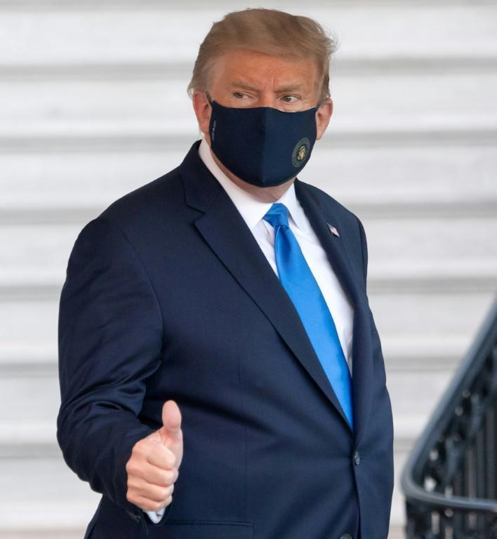 US President Donald Trump gives a thumbs up as he walks to Marine One to head to a military hospital in the Washington suburbs, where he will work for several days as doctors monitor his condition