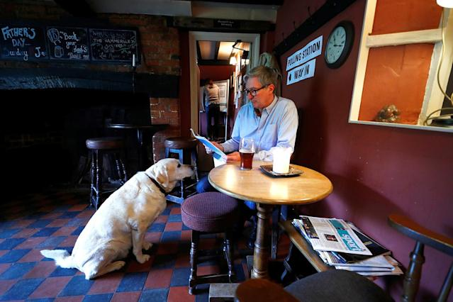 <p>A man sits with his dog inside the Fox and Hounds public house used as a temporary polling station in Christmas Common, Britain, June 8, 2017. (Photo: Eddie Keogh/Reuters) </p>