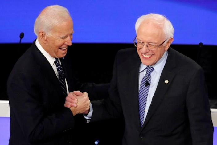 Democratic 2020 U.S. presidential candidates former Vice President Joe Biden greeets Senator Bernie Sanders as they take the stage for the seventh Democratic 2020 presidential debate at Drake University in Des Moines