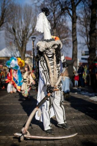 """Amid the din, the Grim Reaper cuts a calm figure as he waves his scythe at onlookers, although popular tradition has it that death merely marks the passage to """"a new and higher stage of life,"""" says ethnographer Barbara Rosiek"""
