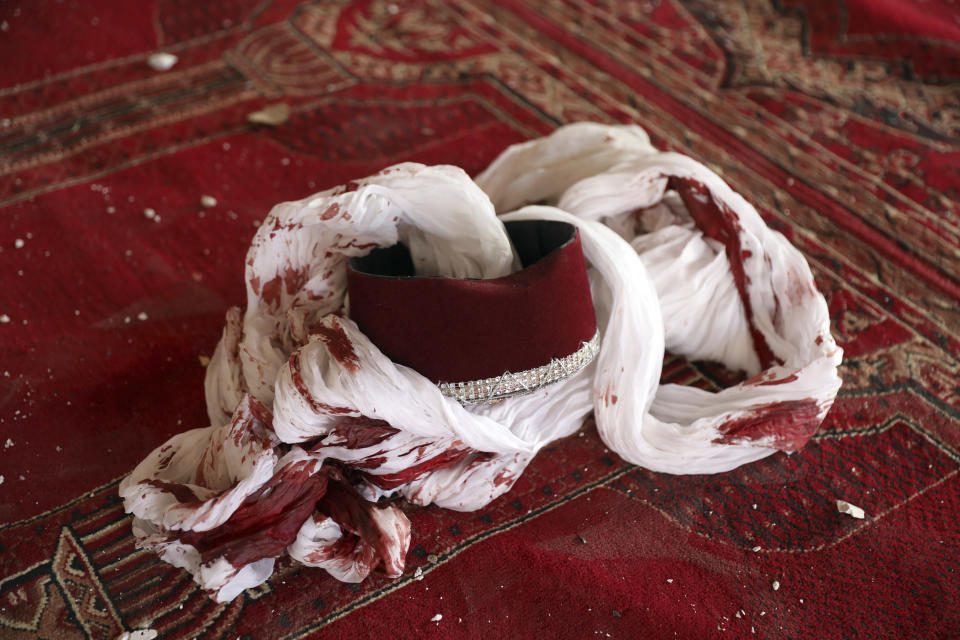 A blood-stained turban and cap are seen inside a mosque after a bomb explosion in Shakar Dara district of Kabul, Afghanistan, Friday, May 14, 2021. A bomb ripped through a mosque in northern Kabul during Friday prayers killing 12 worshippers, Afghan police said. (AP Photo/Rahmat Gul)