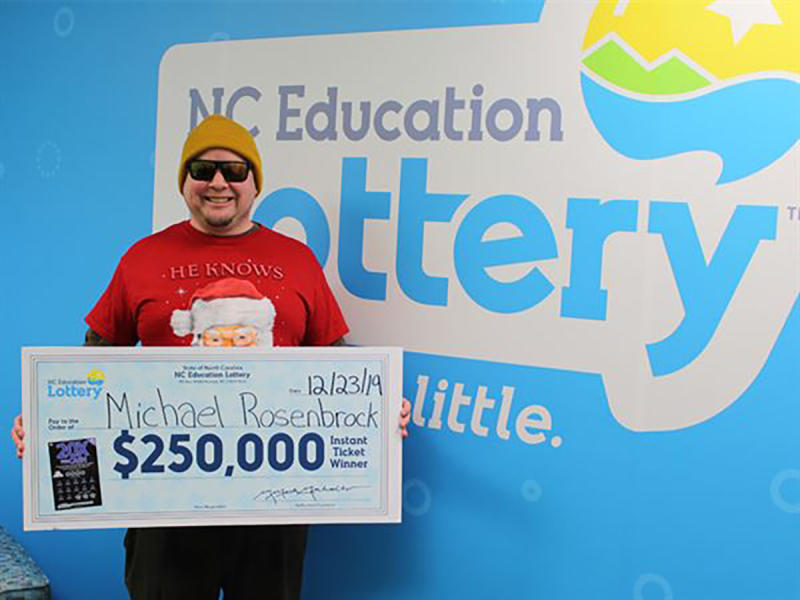This Monday, Dec. 23, 2019 photo provided by N.C. Education Lottery shows Michael Rosenbrock of Mint Hill, N.C. holding an oversized check after winning $250,000 from a lottery ticket in Raleigh. Rosenbrock won after stopping by a grocery store to buy some last-minute fixings for Christmas dinner. North Carolina lottery officials said in a statement that Rosenbrock claimed his prize on Monday. (N.C. Education Lottery via AP)