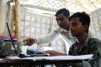 Mohib Ullah, a Rohingya Muslim leader of the Arakan Rohingya Society for Peace and Human Rights helps a computer operator at his office in Kutupalong refugee camp in Ukhiya, Cox's Bazar