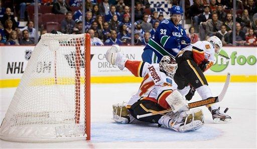 Calgary Flames goalie Miikka Kiprusoff, lower left, of Finland, makes a toe save as Mark Giordano, right, defends against Vancouver Canucks' Henrik Sedin, of Sweden, during the first period of an NHL hockey game game in Vancouver, British Columbia, on Wednesday, Jan. 23, 2013. (AP Photo/The Canadian Press, Darryl Dyck)