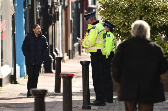 Police community support officers talk to a man on a street in Brighton shortly after the lockdown (AFP)