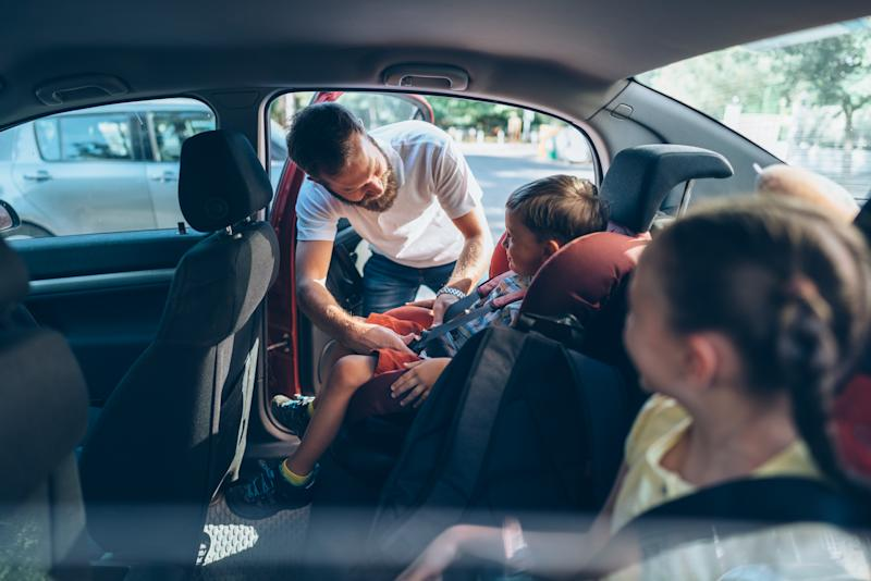 Father caring his kids to be safe during road trip