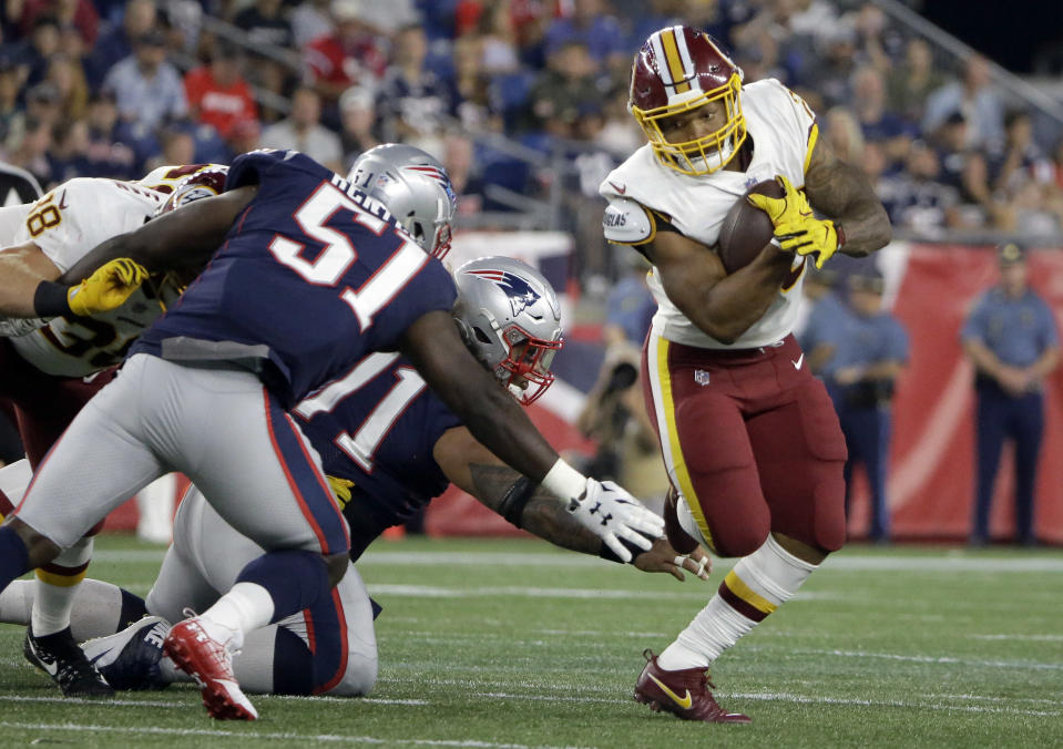 Washington Redskins running back Derrius Guice, right, evades New England Patriots linebacker Ja'Whaun Bentley (51) and defensive tackle Danny Shelton, center, during the first half of a preseason NFL football game, Thursday, Aug. 9, 2018, in Foxborough, Mass. (AP Photo/Steven Senne)