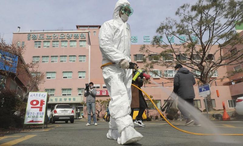 A worker in protective gears sprays disinfectant outside Daenam Hospital in Cheongdo, South Korea, on Friday.