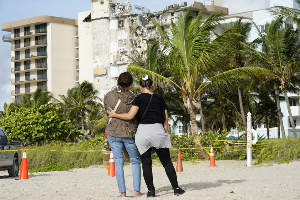Maria Fernanda Martinez, left, and Mariana Corderiro, right, of Boca Raton, Fla., stand outside of a 12-story beachfront condo building which partially collapsed, Friday, June 25, 2021, in the Surfside area of Miami. The apartment building partially collapsed on Thursday.(AP Photo/Lynne Sladky)