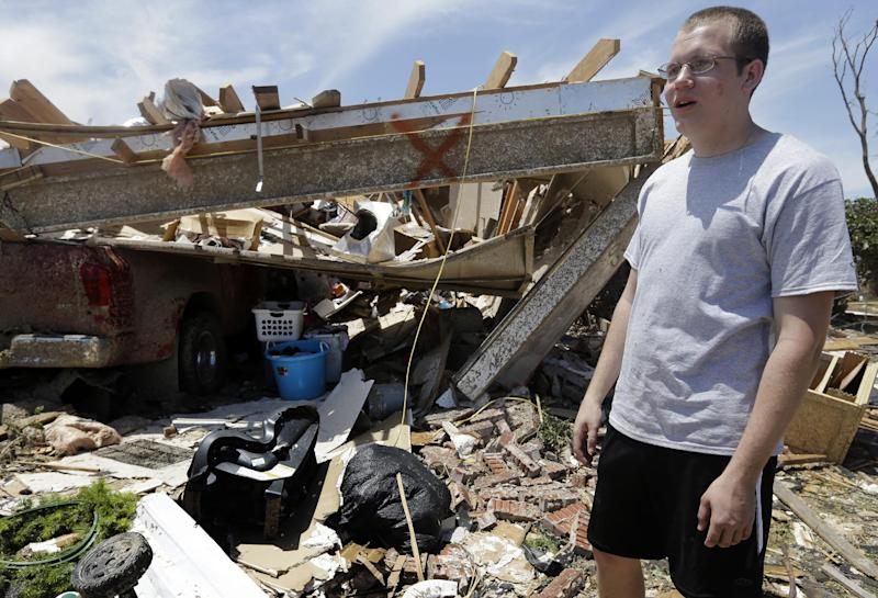 In this May 22, 2013 photo, Zack Bagensie stands near his neighbor's garage, in Moore, Okla., that was destroyed with the rest of the home as he responds to a reporter's questions about how his father took refuge from Monday's tornado in the storm shelter that lies beneath the blue and white plastic buckets. (AP Photo/Tony Gutierrez)