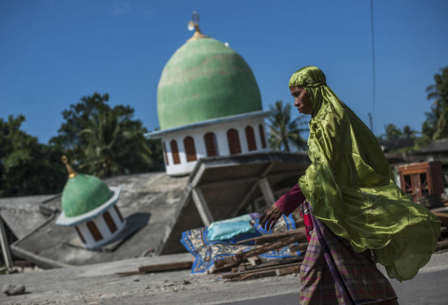 <p>A Muslim woman walks past a mosque collapsed during Sunday's earthquake in Gangga, Lombok Island, Indonesia, Saturday, Aug. 11, 2018. (Photo: Fauzy Chaniago/AP) </p>