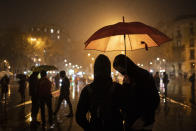 Demonstrators take cover from the rain as they gather ahead of a protest condemning the arrest of rap artist Pablo Hasél in Barcelona, Spain, Monday, Feb. 22, 2021. Pablo Hasel spent 24 hours barricaded in a university building before police took him away last week to serve a 9-month prison sentence for insulting the Spanish monarchy and praising terrorist violence in his music. (AP Photo/Felipe Dana)