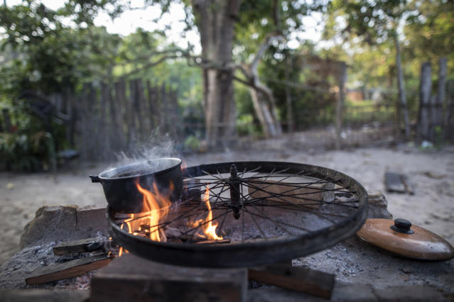 In this Sept. 5, 2019 photo, a Tembe family cooks breakfast asa pot boils on top of a bicycle wheel serving as a grill outside their home in the Tekohaw village, in Para state, Brazil. The Tembe hunt with bows and arrows, fish for piranhas and gather wild plants. They also watch soap operas on TV or check the internet on phones inside thatch-roof huts. (AP Photo/Rodrigo Abd)