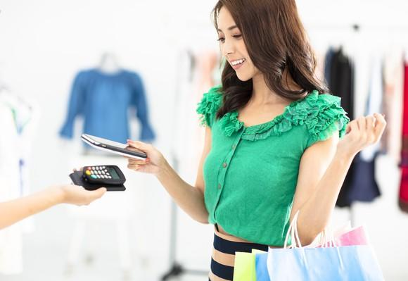A woman pays for a purchase with a smartphone.