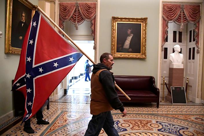 A supporter of President Donald Trump carries a Confederate battle flag on the second floor of the U.S. Capitol near the entrance to the Senate after breaching security defenses, in Washington, U.S., January 6, 2021.         (Mike Theiler/Reuters)