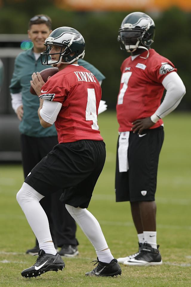 Philadelphia Eagles quarterback Michael Vick, right, looks on as G. J. Kinne throws a pass during practice at the NFL football team's training facility, Tuesday, Oct. 22, 2013, in Philadelphia. (AP Photo/Matt Rourke)