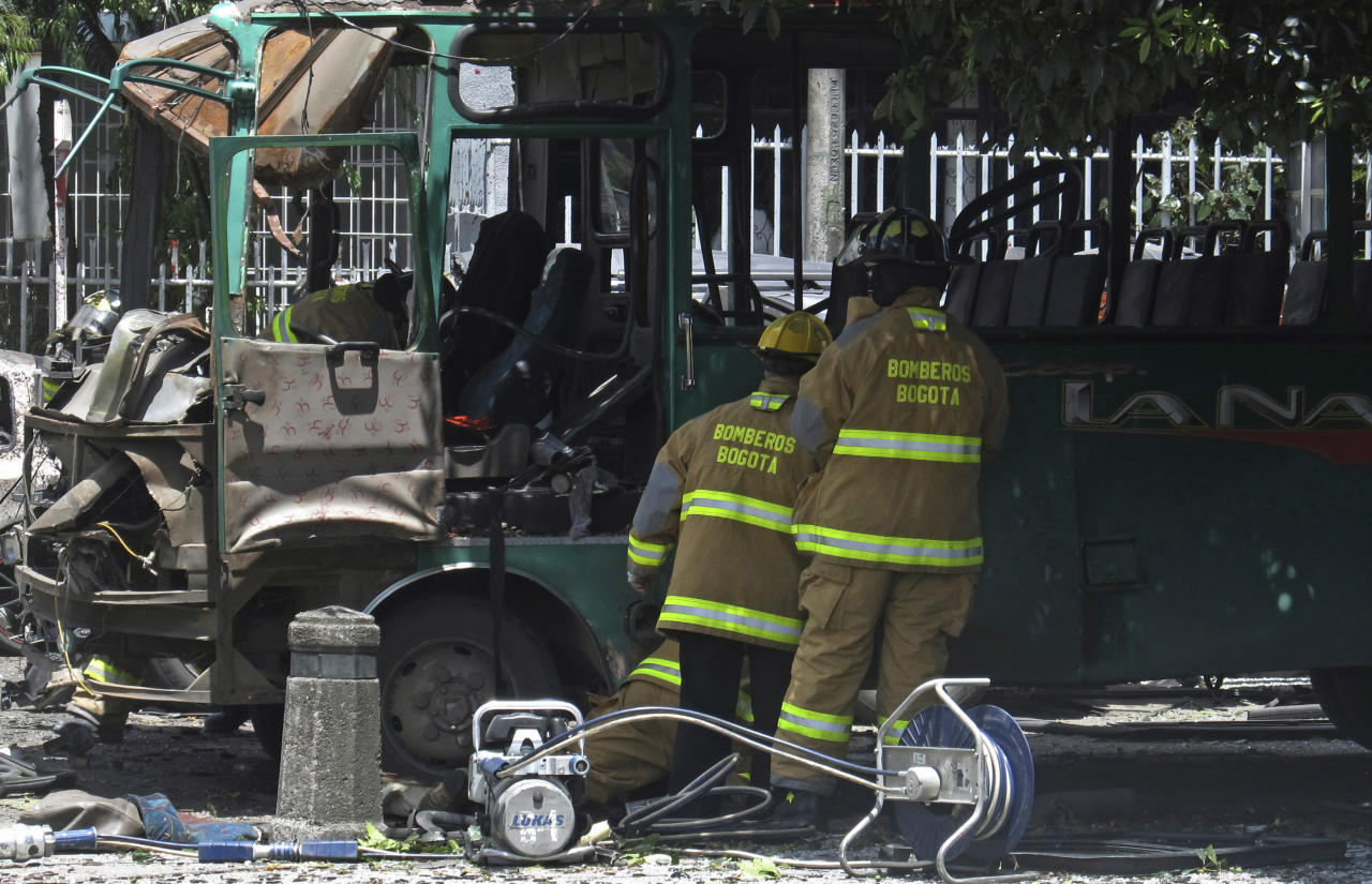 Firefighters inspect a damaged bus at the scene of a bomb attack in Bogota, Colombia, Tuesday, May 15, 2012. A bomb targeting a former Colombian interior minister killed two people on Tuesday and injured at least 19 others in the heart of Bogota's commercial district, authorities said.(AP Photo/Ricardo Mazalan)