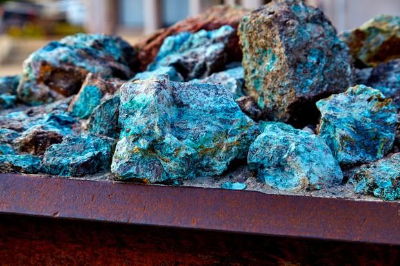 Copper ore piled on a flat metal surface
