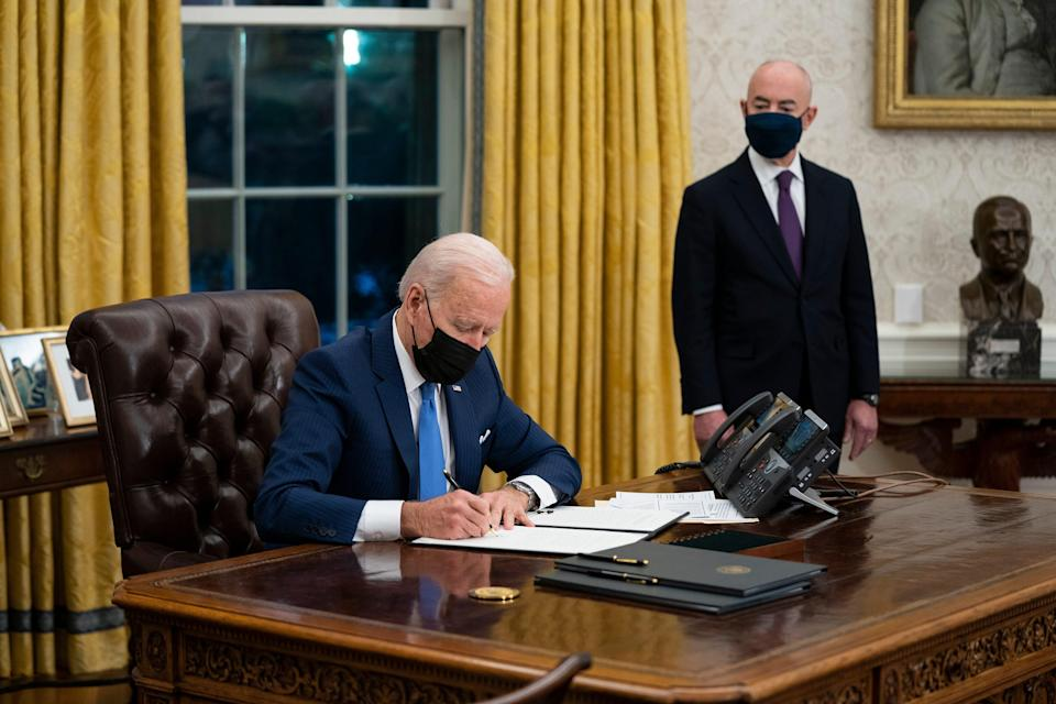 President Joe Biden, photographed with Homeland Security chief Alejandro Mayorkas in the Oval Office on Feb. 2,  will offer temporary legal protections to as many as 300,000 Venezuelans now living in the United States.
