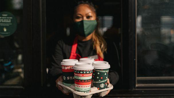 PHOTO: A Starbucks employee holds a tray of holiday drinks. (Starbucks)