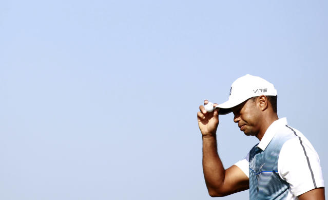 Tiger Woods of the US touches his hat as he walks off the 1st green during the first day of the British Open Golf championship at the Royal Liverpool golf club, Hoylake, England, Thursday July 17, 2014. (AP Photo/Peter Morrison)