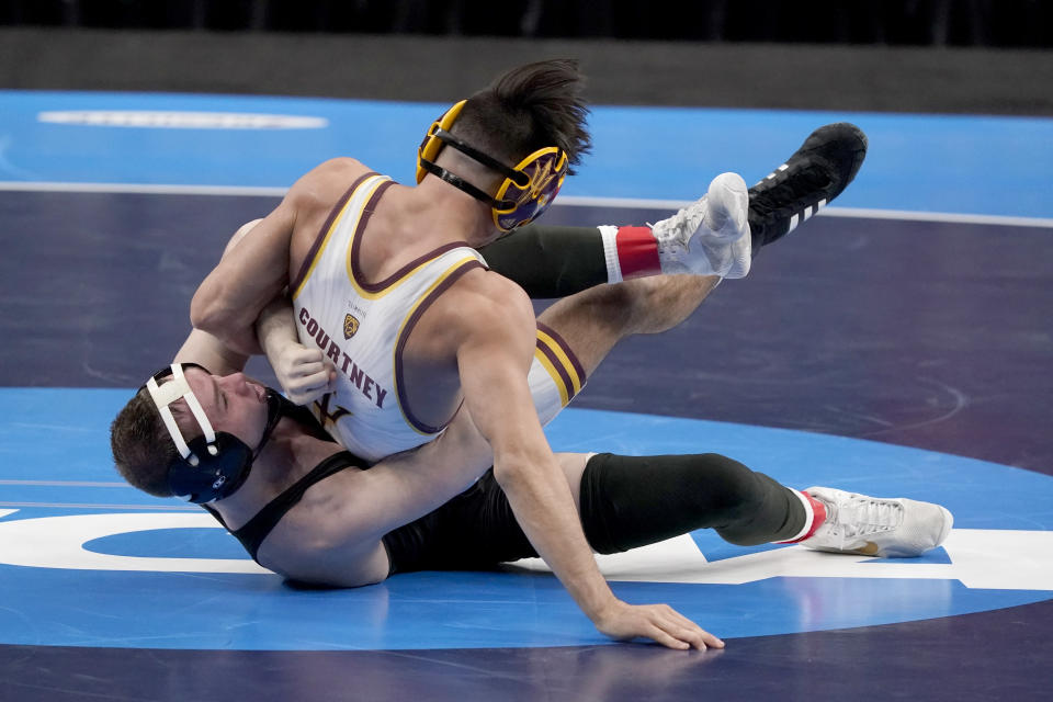 Iowa's Spencer Lee, bottom, takes on Arizona State's Brandon Courtney during their 125-pound match in the finals of the NCAA wrestling championships Saturday, March 20, 2021, in St. Louis. (AP Photo/Jeff Roberson)