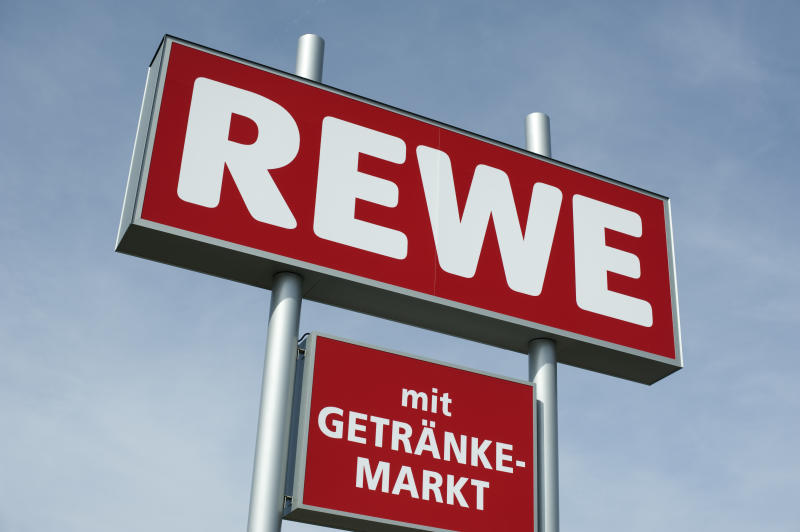 """Limeshain, Germany - March 28, 2012: REWE Sign outside a REWE supermarket.The REWE group is the second biggest food trader in Germany. REWE is a German Supermarket chain and headquartered at Cologne. It is part of the REWE Group which operates in 14 European countries."""